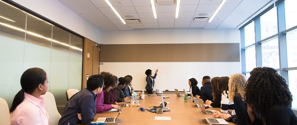 Group of people at a table watching a woman present at a white board