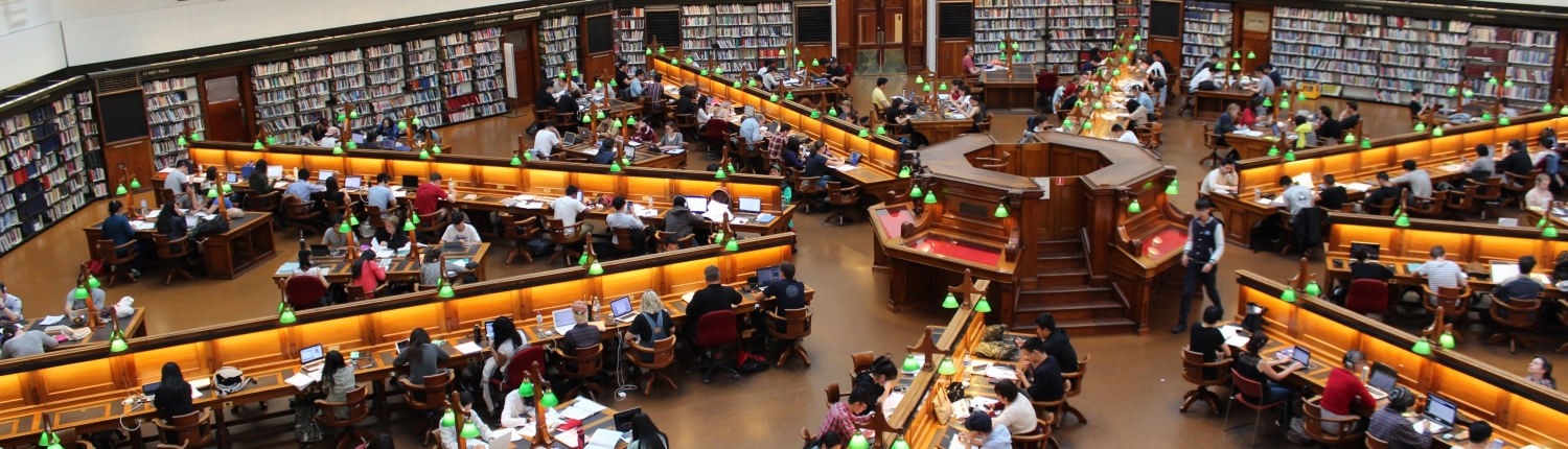 Birdseye view of library filled with people at desks reading