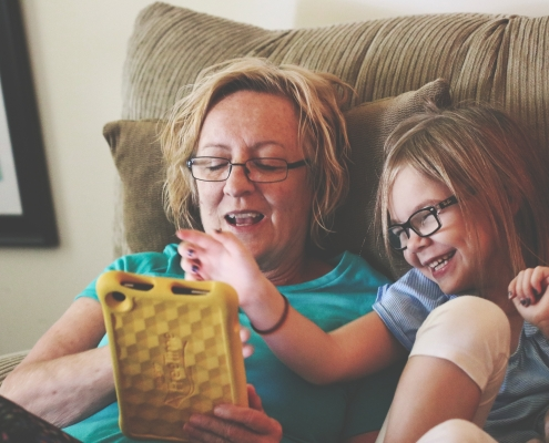Parent and child using a tablet on the couch together